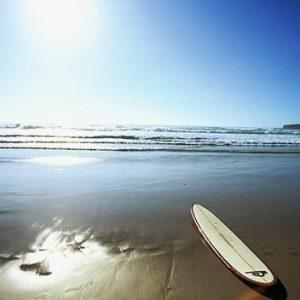 photo-thematique-une-planche-sur-le-sable-les-vagues-au-loin